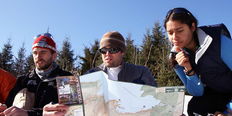 Cross-country skiers consulting a trail map