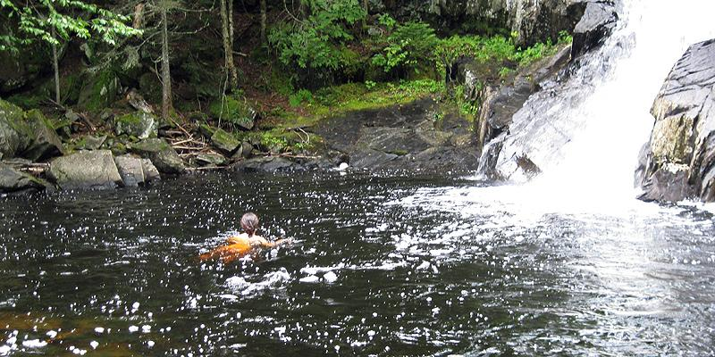 Swimming at the foot of a waterfall